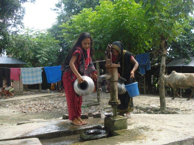 Women carrying water from a public water tap in a periurban neighbourhood