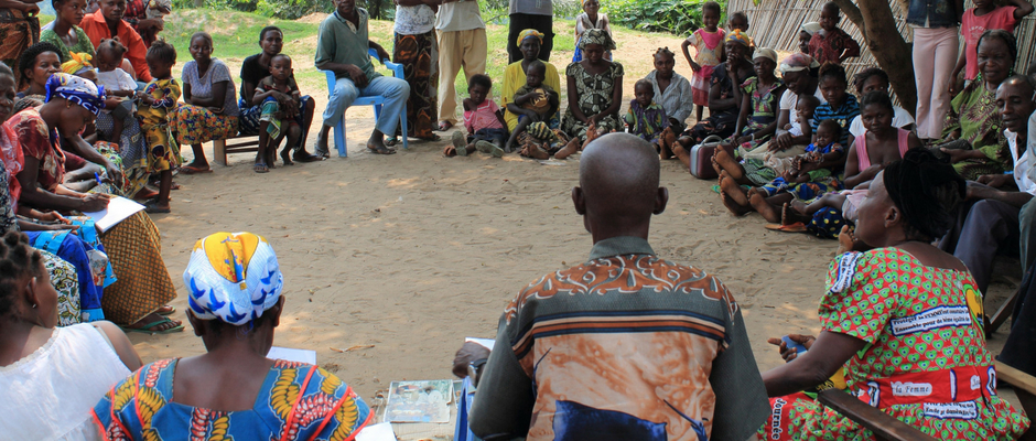 A community group meets under the shade of a mango tree in the Democratic Republic of Congo.