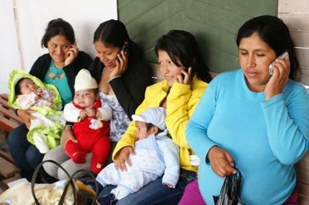 Four women, with their babies on their laps, using their phone