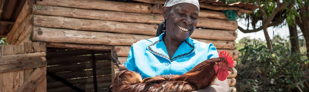 Woman holding a chicken on her farm.