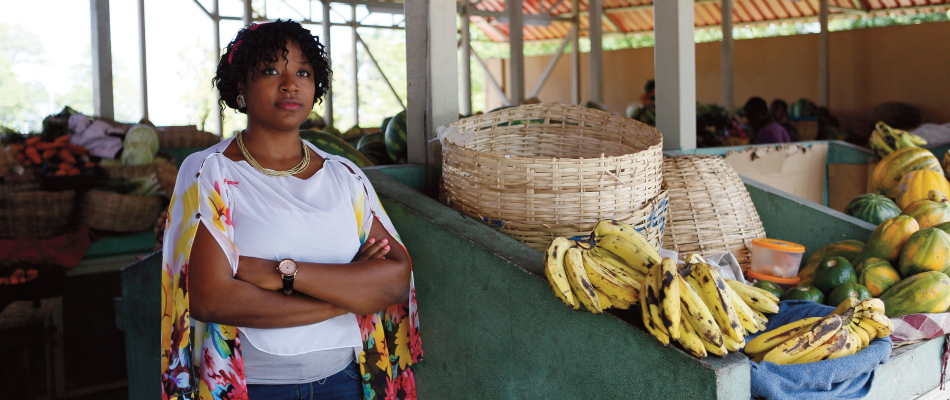 a hatian woman standing in front of a fruit stand